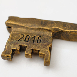 A wrought iron key in golden patina