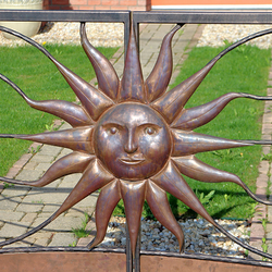 A hand wrought iron gate with the embossed sun - a detail - luxury gates