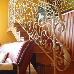 A hand wrought iron interior staircase railing - A white railing with gold-green patina