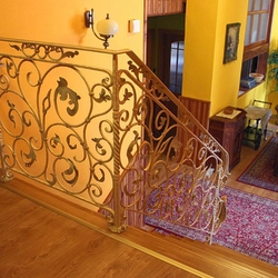 A wrought iron white railing with gold-green patina