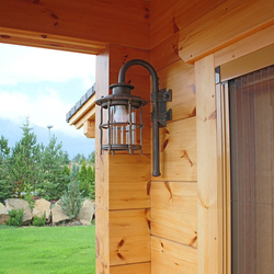 A wrought iron wall lighting in a mountain cottage patio - luxury outdoor lamp