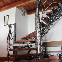 An artistic staircase with railing called TREE forged of natural materials iron and wood - modern interior railing