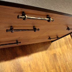 Forged handles on kitchen cabinet - detailed view on wrought iron work