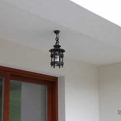 A wrought-iron hanging light HISTORICAL in the exterior of a family house - luxury lights