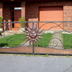 A wrought-iron gate with embossed sun forged for a family house