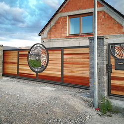 Sliding gate in a family house - hand-forged gate in combination with cedar wood