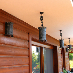 Original pendant and wall lighting in the shape of tree bark on the terrace of the cottage