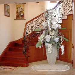 A romantic wrought iron railing with a wooden handrail
