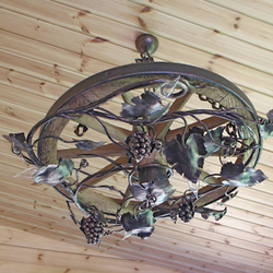 An exceptional hand wrought chandelier of a vine design is forged into the wagon wheel