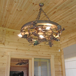 Stylish chandelier in enclosed summer house in mountain cottage – hand-wrought iron work of art with an UKOVMI seal