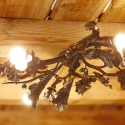 A ceiling light in the shape of an oak - a luxurious hand wrought iron chandelier from UKOVMI