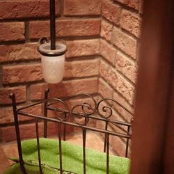 A wrought iron toilet brush holder