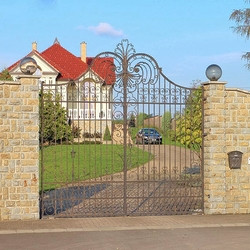 An exclusive wrought iron gate and fence in a family villa - A forged gate in historical style