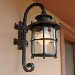 A wrought iron lamp with glass