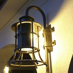 A wrought iron lamp with a shade