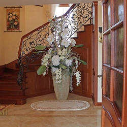 A wrought iron railing with a wooden handrail