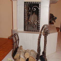 A wrought iron firewood rack with fireplace tools