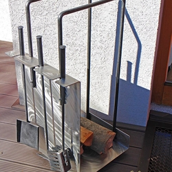A modern stainless steel firewood rack with fireplace tools