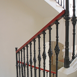 Hand wrought iron interior staircase railing with a wooden handrail